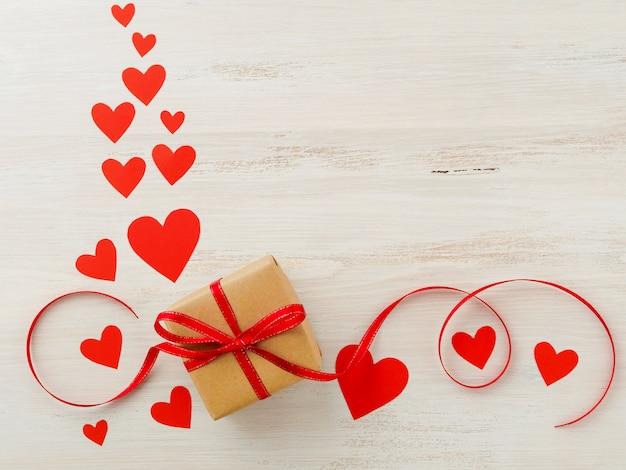 Simbolo del giorno di san valentino - confezione regalo su sfondo rosa con cuori, vista dall'alto, copia spazio per il testo