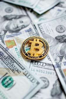 Una simbolica monete di bitcoin su banconote da cento dollari. scambia bitcoin in contanti con un dollaro.