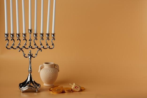 Simboli della festa ebraica su uno sfondo di pesca hanukkah un barattolo di candele caramelle dreidel di legno