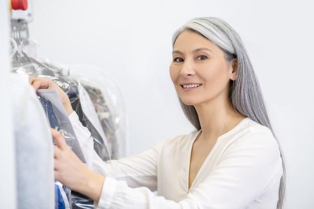 Simpatica donna adulta con lunghi capelli grigi in piedi vicino a cremagliera di vestiti di buon umore