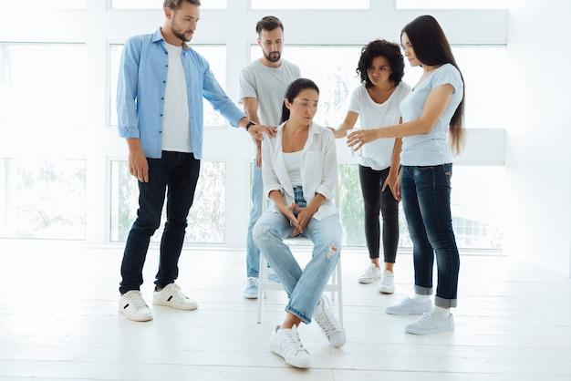Giovani simpatici e simpatici che stanno intorno alla loro amica e la confortano mentre cercano di tirarla su di morale