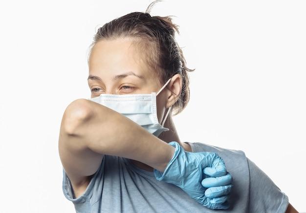 I sintomi dell'influenza. la donna in maschera medica tossisce isolata su un bianco. covid19.