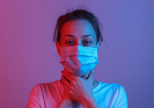 I sintomi dell'influenza. la donna in maschera medica tiene la gola. luce sfumata al neon rosso blu