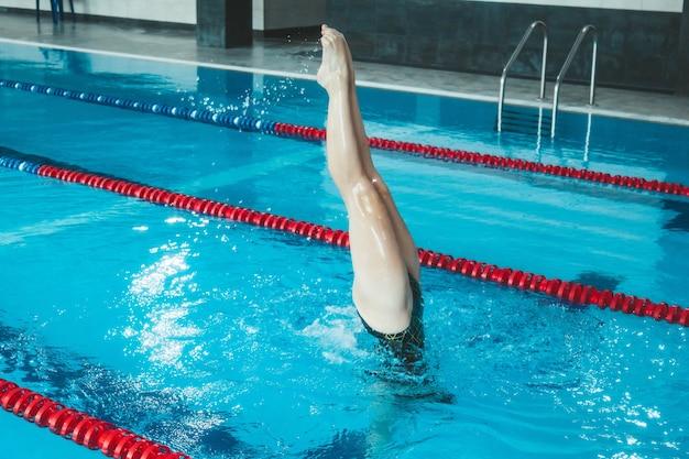Atleta di nuoto sincronizzato si allena da solo in piscina