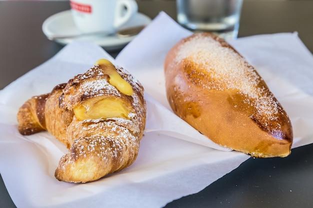 Siracusa in sicilia, italia. tradizionali brioches fresche con panna servite al tavolo del bar come colazione. luce naturale, niente studio.