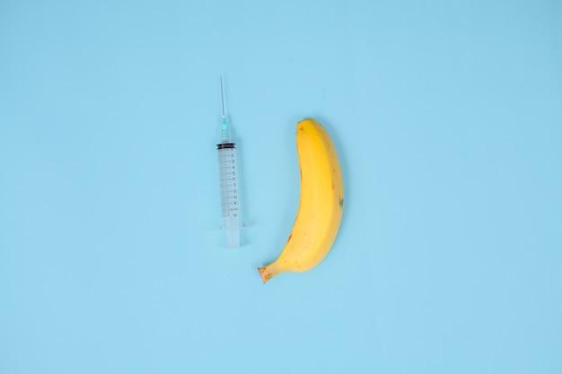 Siringa, banana e contraccezione isolati su sfondo blu