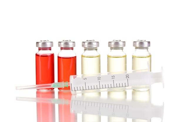 Siringa e fiale mediche su bianco