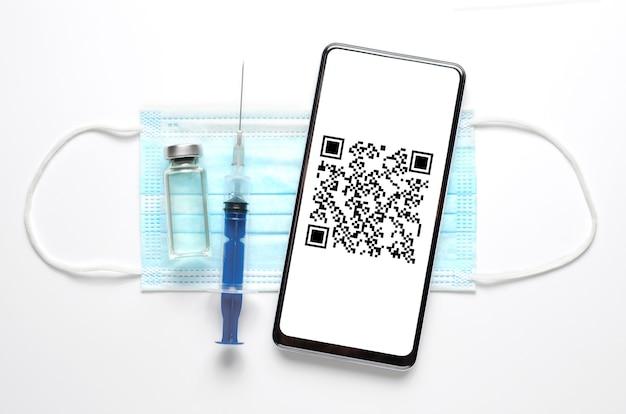 Una siringa, uno smartphone e una mascherina medica. codice qr sullo schermo del telefono. il concetto di protezione e vaccinazione contro l'infezione virale. vista piatta dall'alto. sfondo bianco
