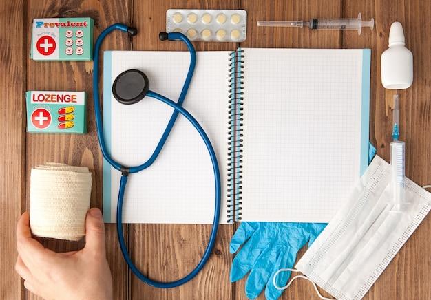 Siringa, stetoscopio, blocco note pagina vuota, benda, pillola, benda elastica e guanti sul tavolo medico. diagnosi medica o prescrizione medica