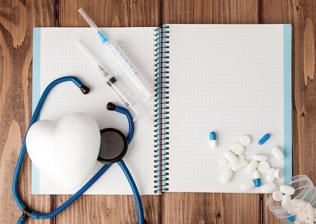 Siringa, stetoscopio, blocco note della pagina vuota e pillola sul tavolo del medico