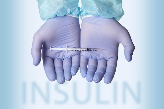 Una siringa con insulina giace sui palmi con guanti di lattice sullo sfondo della scrittura di insulina