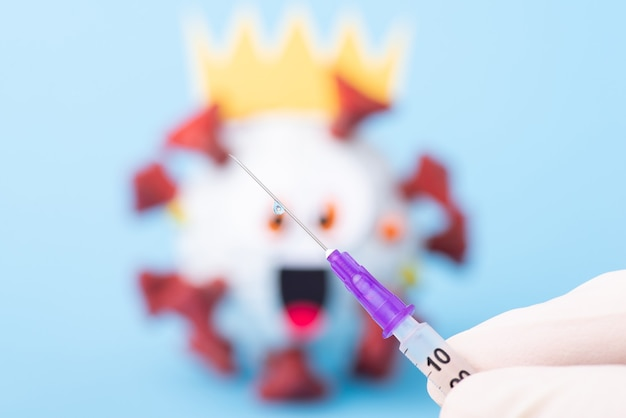 Siringa con vaccino in mano di un uomo, piccola goccia sull'ago