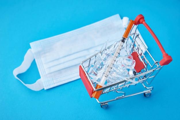 Siringhe e fiale con la medicina in un carrello della spesa e mascherina medica su sfondo blu. acquisto di medicinali cocept