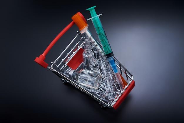 Siringhe e fiale con la medicina in un carrello della spesa. acquisto di medicinali cocept