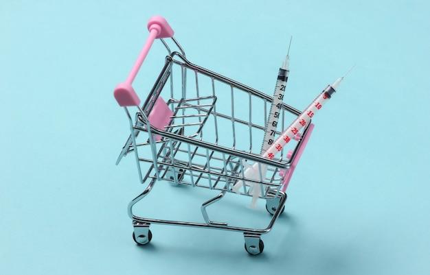 Siringhe in un carrello per supermercati su una superficie blu