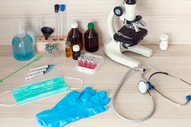 Siringhe, vaccini, microscopio, stetoscopio sul tavolo