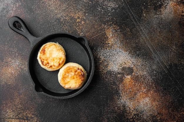 Frittelle di formaggio syrniki su padella in ghisa padella su padella in ghisa, vista dall'alto piatta, sul vecchio tavolo rustico scuro