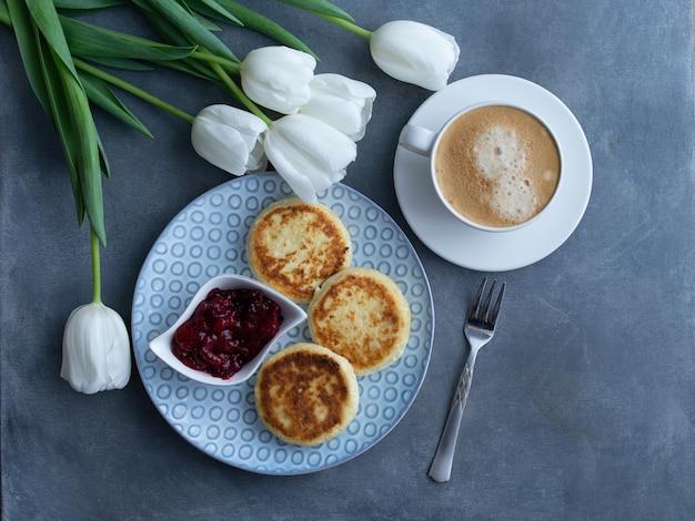Syrniki, cagliata o frittelle di ricotta con marmellata di ciliegie e caffè su sfondo grigio con tulipani bianchi, vista dall'alto. colazione dietetica sana.