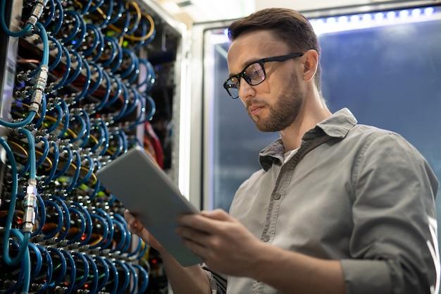 Ingegnere di sistema che utilizza compressa nella stanza del server
