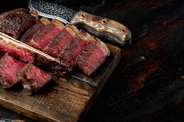 La bistecca con l'osso viene grigliata a fette su un pezzo. set di bistecca di porterhouse barbecue invecchiato, sul tagliere di legno, sul vecchio tavolo in legno scuro