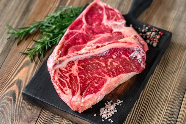 Bistecca con l'osso sulla tavola di legno