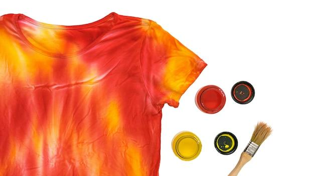 T-shirt in stile tie dye, pennello e vernice isolato su superficie bianca