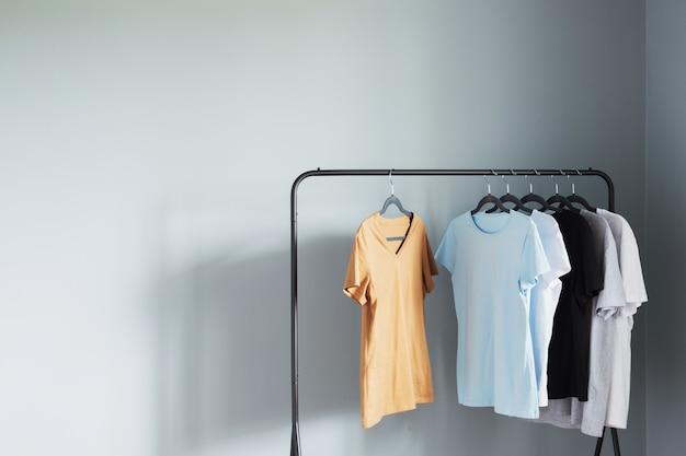 Magliette di colori neutri su appendiabiti nero contro muro grigio