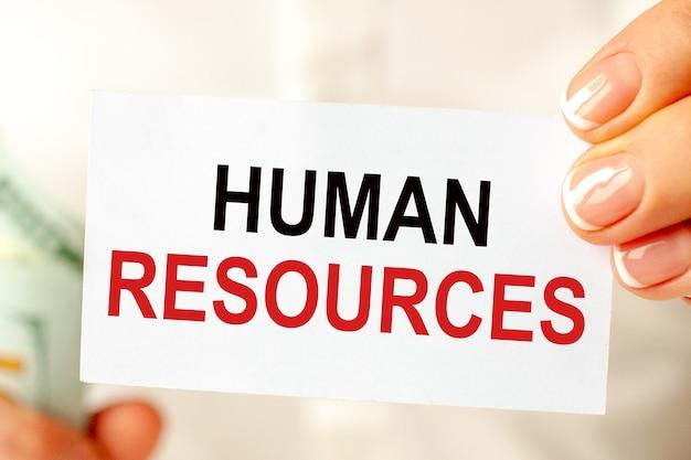 Sul tavolo ci sono le bollette, un pacco di dollari e un cartello su cui è scritto: risorse umane. concetto di affari, finanza ed economia.