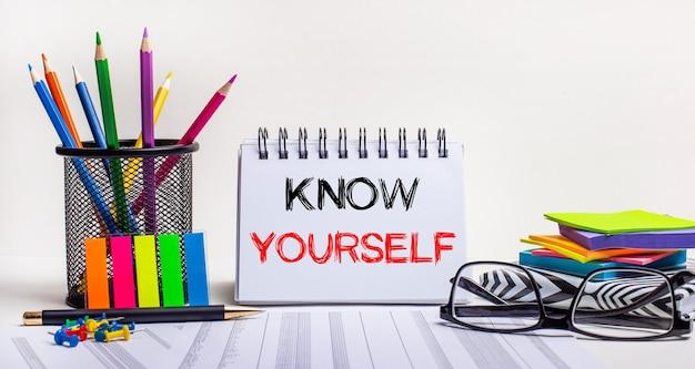 Sul tavolo ci sono matite colorate su supporto, adesivi dai colori vivaci, bicchieri e un quaderno con la scritta conosci te stesso. concetto motivante. chiamare all'azione