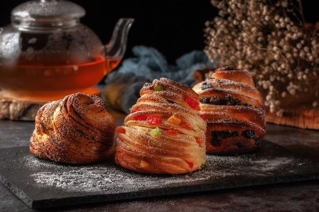 In tavola i kraffins con uvetta, canditi e semi di papavero, cosparsi di zucchero a velo.