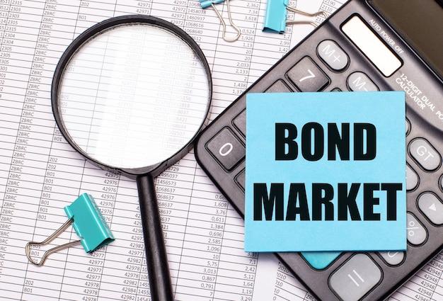 Sul tavolo ci sono rapporti, una lente d'ingrandimento, una calcolatrice e un adesivo blu con le parole bond market. concetto di affari