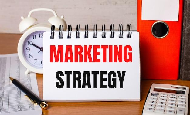 Sul tavolo ci sono report, una sveglia bianca, una calcolatrice, cartelle per fogli, una penna e un quaderno bianco con la strategia di marketing. concetto di affari