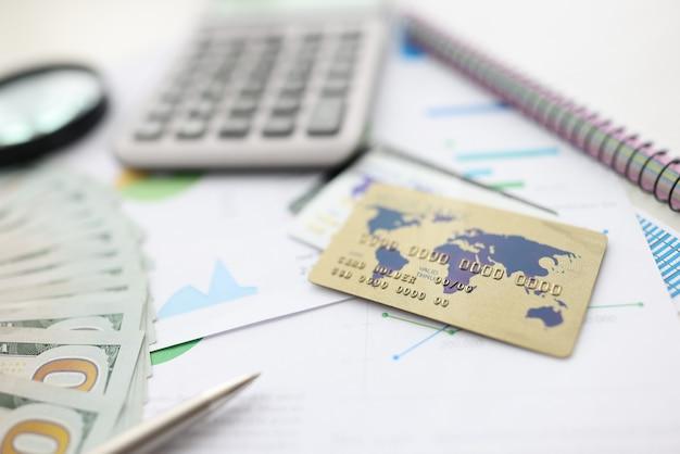 Sulla calcolatrice da tavolo, penna, carta, documenti, taccuino, lente d'ingrandimento e denaro