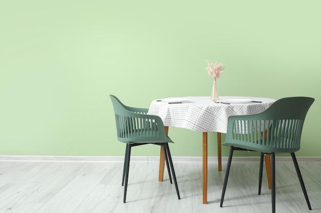 Tavolo e sedie vicino alla parete del colore