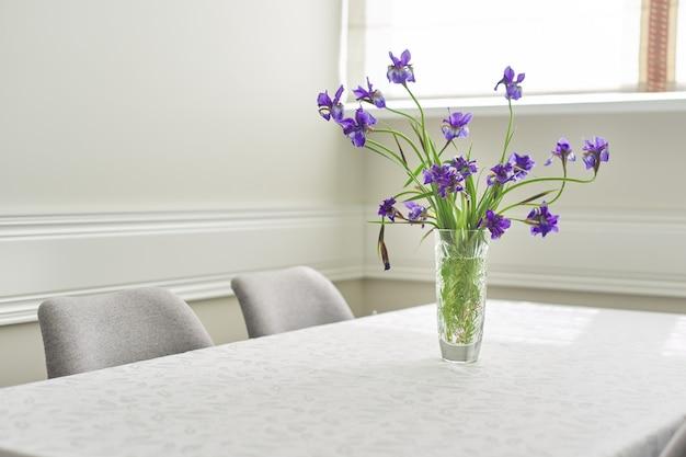 Tavolo e sedie vicino alla finestra, bouquet di iris viola in vaso e tovaglia bianca