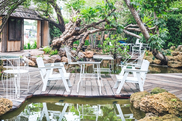 Tavolo e sedie bianche in metallo in un caffè giardino.