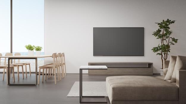 Tavolo sul pavimento di cemento della luminosa sala da pranzo vicino alla zona giorno e divano contro la tv in una moderna casa sulla spiaggia o hotel di lusso.