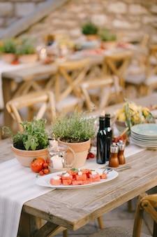 Una tavola imbandita per un evento di gala con un piatto con fette di cocomero vasi di fiori