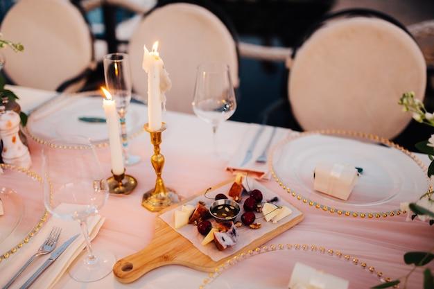 Tavolo decorato con piatti con perline e candele su una tovaglia bianca e ciliegie e formaggio sopra