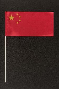 Bandiera da tavolo della cina su sfondo nero. bandiera rossa con stelle. cornice verticale.