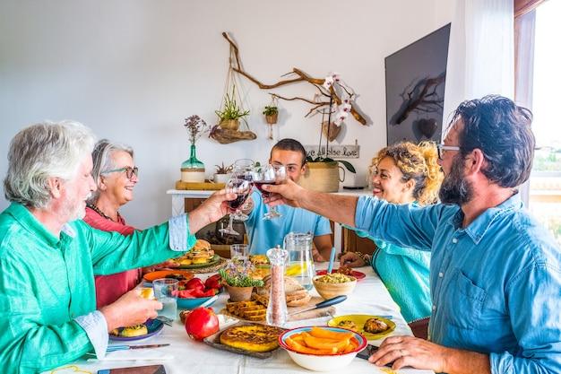 Tavolo pieno di cibo a casa con persone di tutte le età che mangiano insieme e tintinnano con il vino sorridendo e divertendosi - famiglia che pranza in casa