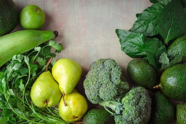 Tavolo pieno di verdure verdi con uno sfondo chiaro e spazio per la copia.