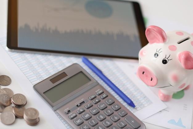 Sul tavolo è il maiale calcolatrice e tablet con monete. offerte vantaggiose sul concetto di depositi