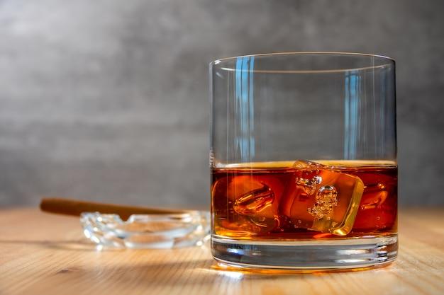 Sul tavolo c'è un bicchiere di whisky con cubetti di ghiaccio. un posacenere con un sigaro sfocato