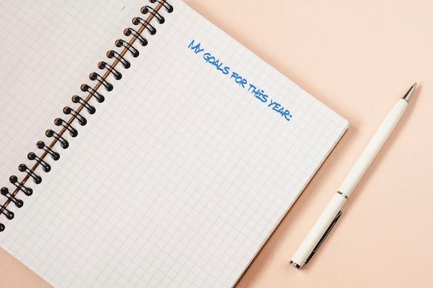 Sul tavolo c'è un taccuino aperto e una penna bianca. i miei obiettivi per quest'anno sono scritti nel taccuino.