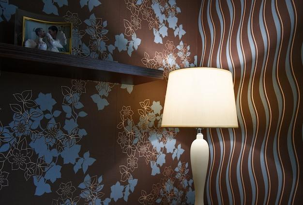 La lampada da tavolo brilla debolmente sul tavolo della camera da letto.