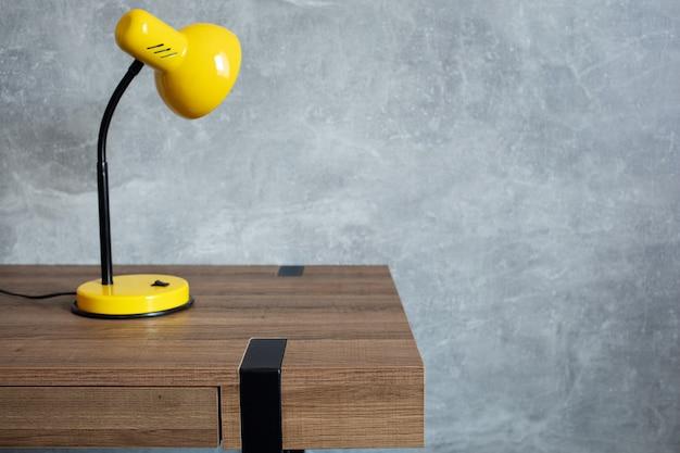 Lampada da tavolo al tavolo di legno vicino alla struttura del fondo del muro di cemento grigio