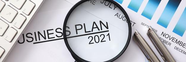 Sul tavolo giace la lente d'ingrandimento e il piano aziendale per il 2021 per mesi. sviluppo e pianificazione aziendale per il concetto del prossimo anno