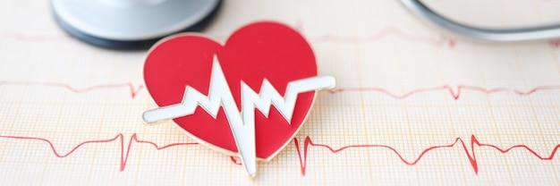 Sul tavolo si trova il cardiogramma dello stetoscopio e il cuore del segno del cuore e il concetto di malattia vascolare