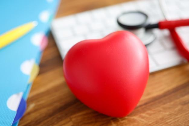 Sul tavolo si trova lo stetoscopio cuore rosso e l'esame della tastiera del sistema cardiovascolare